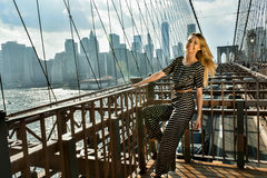 Young smiling model posing at the bridge in hot summer day wearing fashionable jumpsuit. Royalty Free Stock Photography