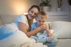 Young smiling mother hugging her baby son before going to sleep. Smiling mother hugging her baby son before going to sleep Stock Photography