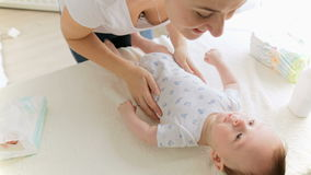 Young smiling mother playing with her baby boy lying on changing table at living room. Camera zooms in stock video