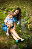 Young smiling mother sit on grass with her little son Stock Image