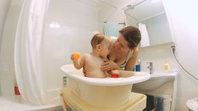 Young smiling mother washing her baby son in bathtub from showerhead stock video footage