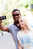 Young smiling multiracial couple taking foto by smartphone Royalty Free Stock Photography