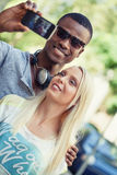 Young smiling multiracial couple taking foto by smartphone Stock Image