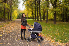 Young smiling mum walks with pram in the autumn yellow park Stock Photos