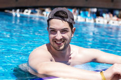 Young smiling muscular man relaxing in the swimming pool. Young smiling  man enjoying his summer vacation  swimming pool Royalty Free Stock Photos