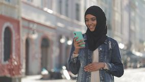 Young smiling muslim woman wearing hijab headscarf standing in the city center and using smartphone. Communication stock video footage