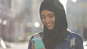 Young smiling muslim woman wearing hijab headscarf standing in the city center and using smartphone. Communication stock video