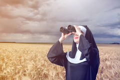 Young smiling nun with binoculars Royalty Free Stock Images