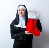 Young smiling nun with Christmas sock. On white background royalty free stock photography