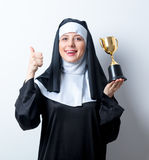 Young smiling nun with golden trophy cup. On white background stock photography