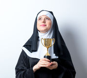 Young smiling nun with golden trophy cup. On white background stock images