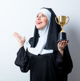 Young smiling nun with golden trophy cup. On white background royalty free stock image