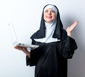 Young smiling nun with laptop computer Royalty Free Stock Images