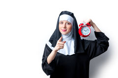 Young smiling nun with red alarm clock Stock Photo