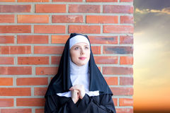 Young smiling nun. On red brick wall background stock images