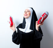 Young smiling nun with red gumshoes Royalty Free Stock Photography