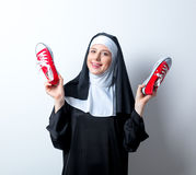Young smiling nun with red gumshoes Royalty Free Stock Image