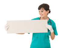Young smiling nurse or doctor showing blank sign Stock Images