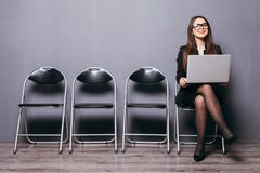 Young smiling office worker woman sitting on wood floor chair using mobile laptop computer prepare interview meeting file in gray royalty free stock photo
