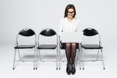 Young smiling office worker woman sitting on wood floor chair using mobile laptop computer prepare interview meeting file isolated royalty free stock photos