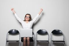 Young smiling office worker woman sitting on wood floor chair using mobile laptop computer with raised hands before prepare interv royalty free stock photos
