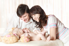 Young smiling parents looking at baby. Play with child. Indoor Stock Images