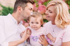 Young smiling parents with their baby outdoor in the park Stock Images