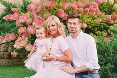 Young smiling parents with their baby outdoor in the park Royalty Free Stock Photos