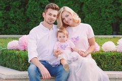 Young smiling parents with their baby outdoor in the park Royalty Free Stock Image
