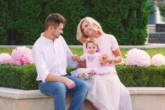 Young smiling parents with their baby outdoor in the park Stock Photo