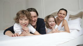 Young Smiling Parents with Two Children are Having Fun Together in Their Bedroom. Joyous Family on White Bed. Young Smiling Parents with Two Children are Having stock video footage