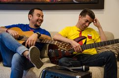Young smiling people playing guitars sitting on a sofa stock photo