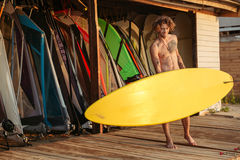 Young smiling professional surfer holding surf board. At the shack Royalty Free Stock Photos