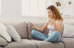 Young redhead girl with digital tablet at home stock image