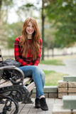 Young smiling redhead woman in red plaid jacket and blue jeans sitting on park bench with blurred park background Royalty Free Stock Photos