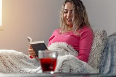 Young relax woman reading book in bed at home. Young smiling relax woman reading book in bed at home Royalty Free Stock Photo