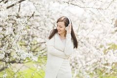 Young smiling relaxed beautiful woman in light casual clothes clinging to headphones listening music in city garden or royalty free stock photography