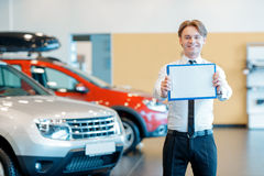 Young smiling salesman with clipboard in car Stock Photography