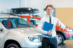 Young smiling salesman with clipboard in car Royalty Free Stock Photo