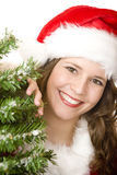 Young smiling Santa Woman near Christmas tree. Young woman dressed as Santa Claus is standing beside a Christmas tree and smiles happy. Isolated on white Royalty Free Stock Photography