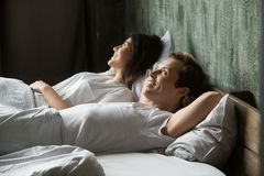 Young smiling satisfied couple in love lying in bed royalty free stock photos