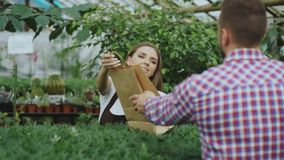 Young smiling seller florist working in garden center. Woman gives shopping bag to customer at store. Indoors Royalty Free Stock Photo