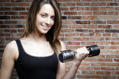 Young smiling woman lifting dumbbells Stock Photos