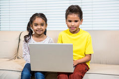 Young smiling siblings using laptop Royalty Free Stock Image
