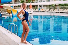 A young smiling slender woman in a dark blue sports swimsuit is standing by the outdoor pool in the hotel in the summer. Woman in royalty free stock image