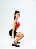Young smiling sport woman doing squats with dumbbells Royalty Free Stock Photo