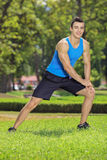 Young smiling sportsman exercising in a park Stock Photos