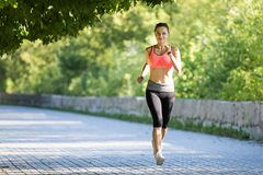 Beautiful young woman in pink top jogging in park. Young smiling sporty woman running in park in the morning. Fitness girl jogging in park stock photography