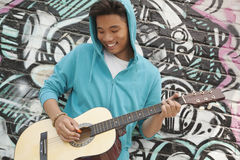 Young smiling street musician leaning on a wall with graffiti drawings and playing his guitar Stock Photos