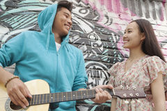 Young smiling street musician leaning on a wall with graffiti drawings, playing his guitar, and flirting with a young woman in a d Stock Image